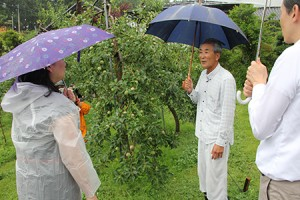 樋ノ田果樹園にてパソナグループ役員のみなさんに説明をするりんご農家の熊谷賢一さん