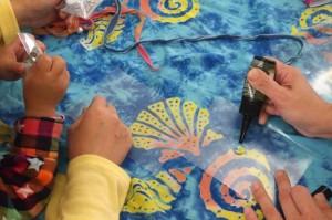 子どもたちと一緒にUVレジン(紫外線に当てると固まる素材)を使ったアクセサリーの試作に挑戦
