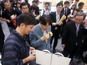 台湾での展示会にてアワビをPRする下苧坪さん(左)。食べて違いを実感してもらう。