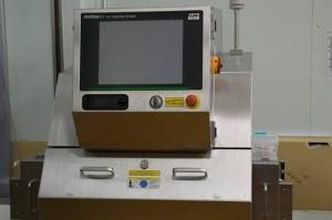 商品をビニール梱包後、再度、X線検査機を通して品質検査を行う