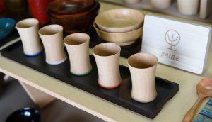 (シナ材の木目を生かしたTsubaki_ liquer cup:手前の5つ 家族や仲間が同じ器で楽しめるよう無色・青・白・緑・赤と塗りが施されています。)