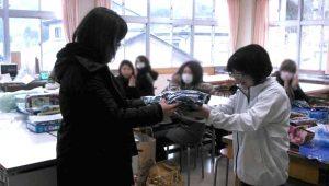 毎年3月に、小学校で社員から保護者へ体操着を手渡しするセレモニーを行っています。