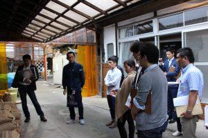 原発事故後の苦境を語る若松味噌醤油店の若松さん(左から2番目)の説明に、参加社員は熱心に耳を傾けていた。